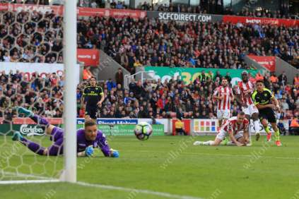 Alexis Sanchez of Arsenal scores their 3rd goal against Stoke