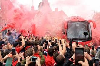 Liverpool fans set flares off as the team bus approaches the stadium