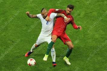Arturo Vidal of Chile battles with Andre Gomes of Portugal