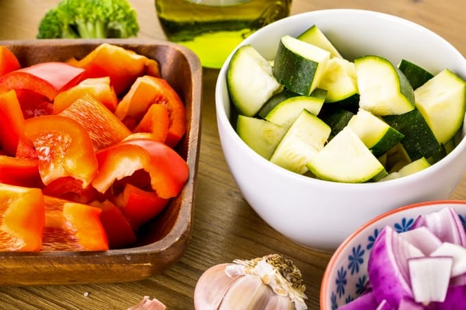 Fresh vegetables (red bell pepper, zucchini, onion) chopped in bowls