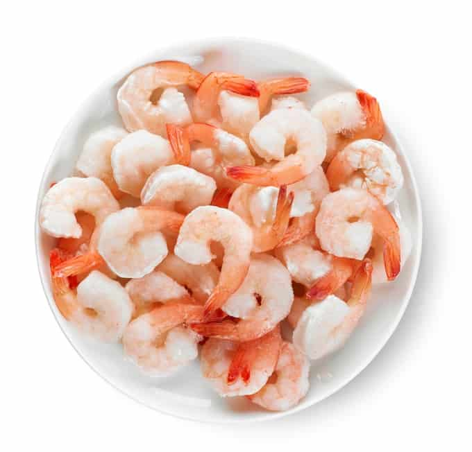 Plate of frozen prawns isolated on white background, top view