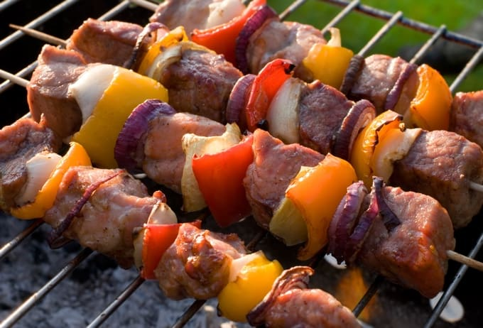 Pork kabob skewers with peppers and onions on a grill