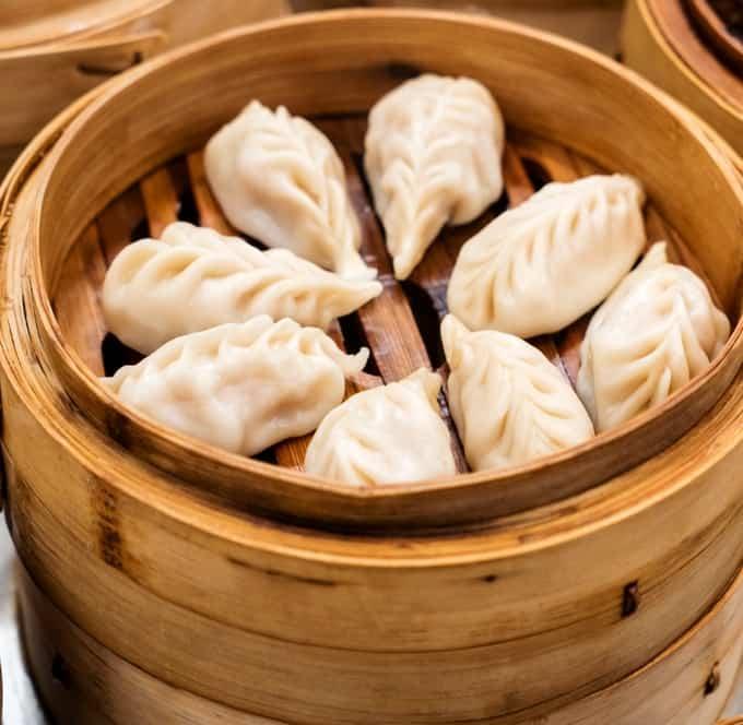 Bamboo steamer basket with vegetable dumplings.
