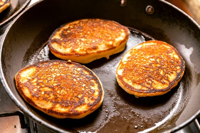 Cooking three banana pancakes in frying pan.