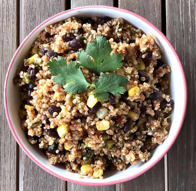 Quinoa salad with corn, black beans, salsa and garnished with fresh cilantro in bowl from above.