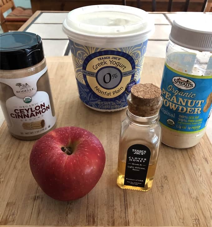 Cinnamon, plain Greek yogurt, peanut powder, honey and a fresh apple on bamboo cutting board for making apple fries with peanut butter dip.