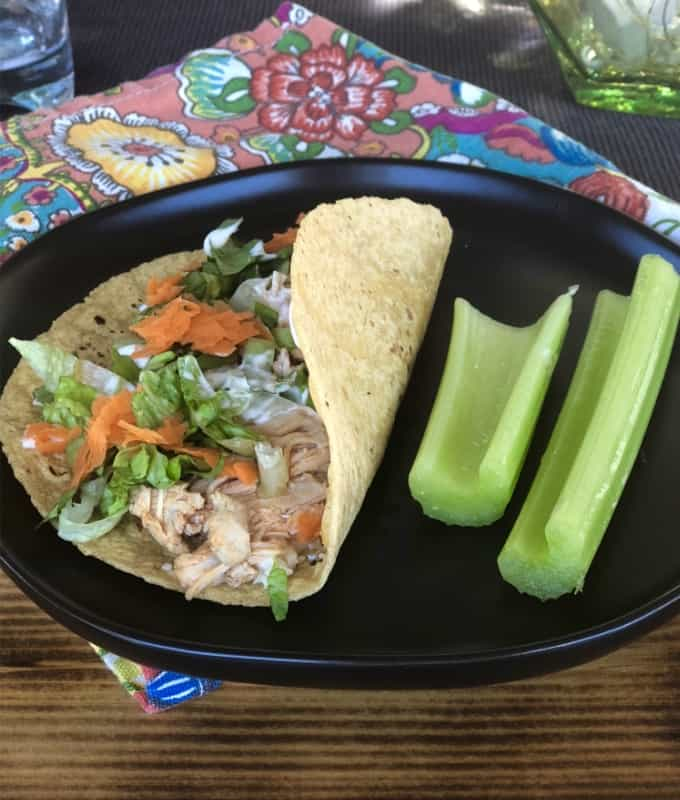 Blue cheese buffalo chicken wrap with celery sticks on black plate.