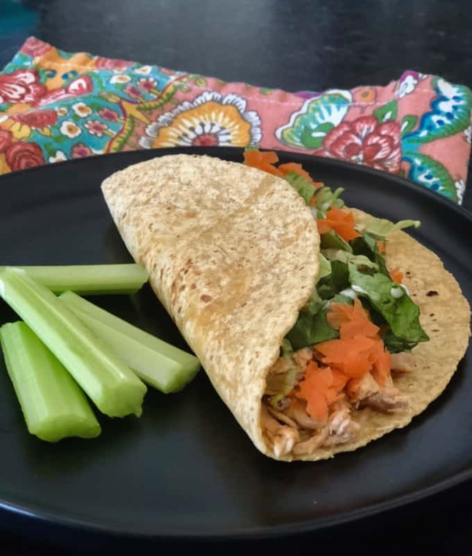 Buffalo chicken blue cheese tortilla wrap with celery sticks on black plate.