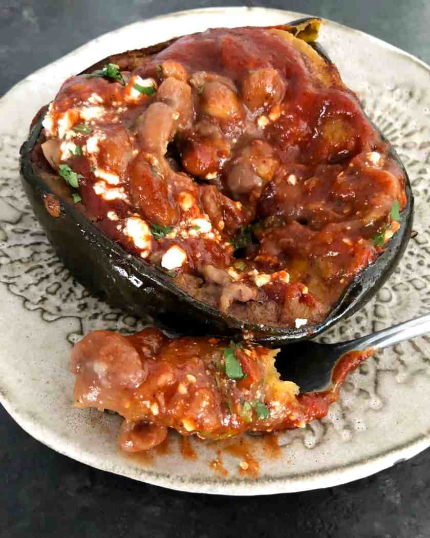 Oven-roasted acorn squash with red chili sauce and pinto beans