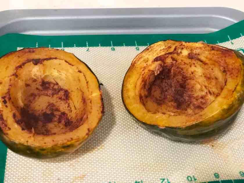 Oven-roasted acorn squash on baking mat lined baking sheet.