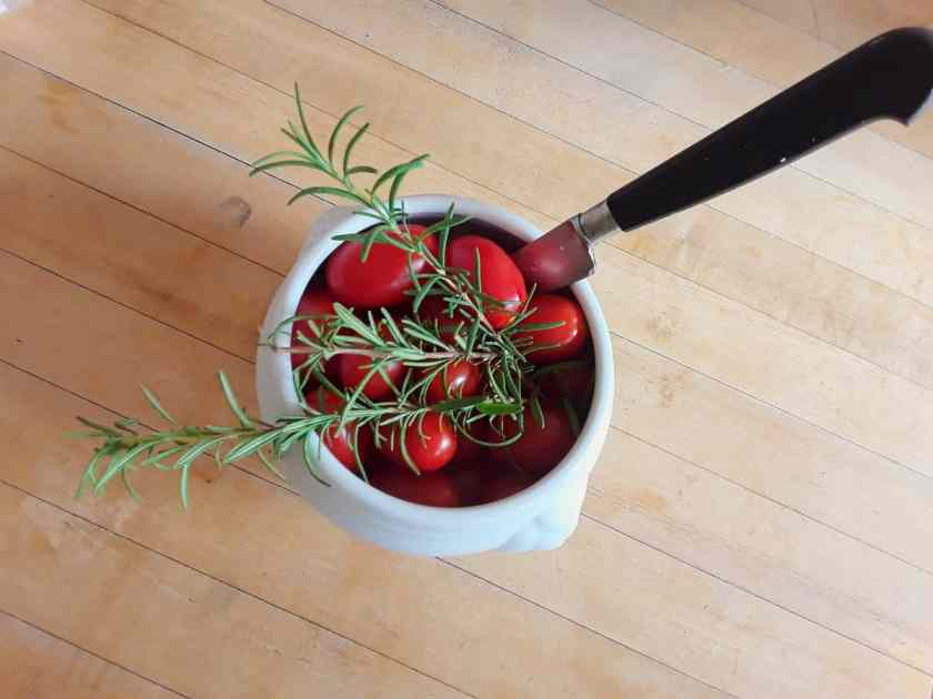 Cherry tomatoes in small white bowl with fresh rosemary and knife.