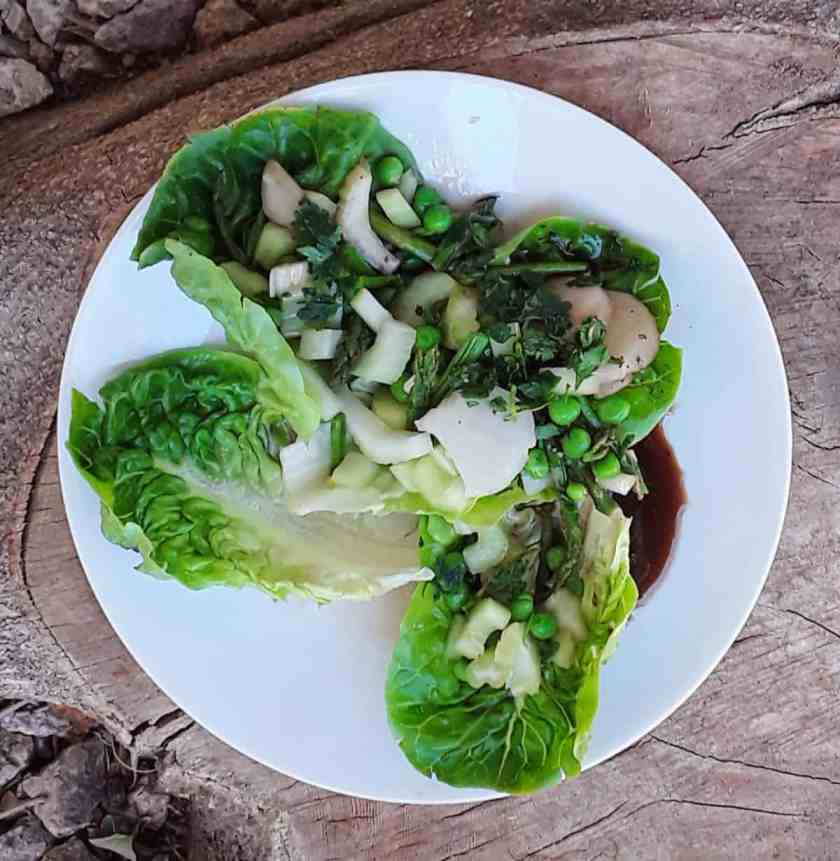 Crunchy Asian-Inspired Green Salad with water chestnuts, celery, asparagus and green peas on white plate.