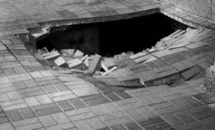 A hole in pedestrian pavement road
