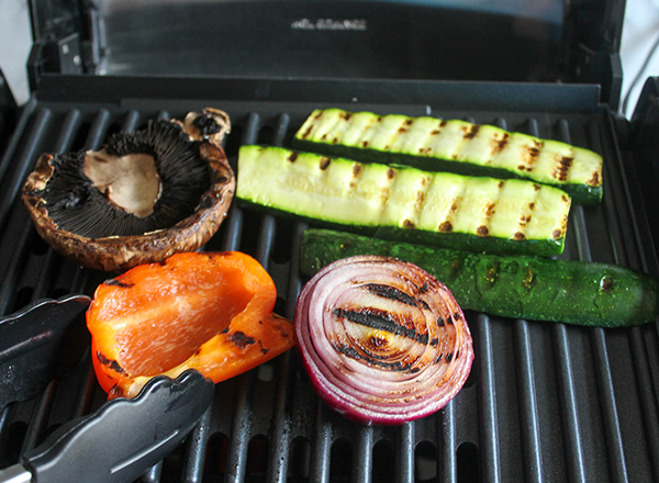 Zucchini peppers mushrooms and onions on a grill
