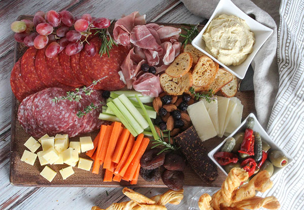 A veiw looking down at a charcuterie board filled with cheese, salami, pepperoni, proscuitto, vegetables and olives
