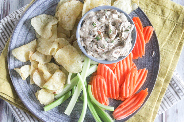 an overhead view of onion dip with chips, carrots and celery sticks