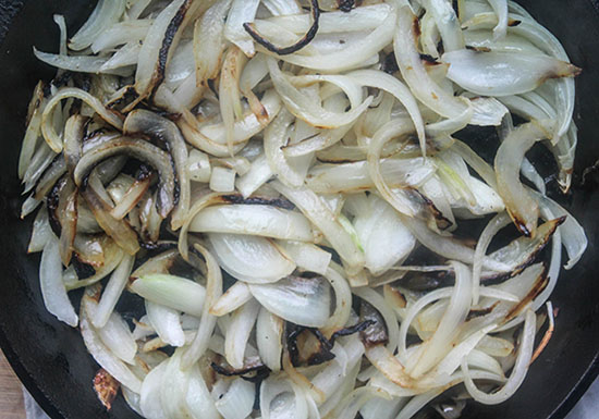 A close up of onions cooking in a pan