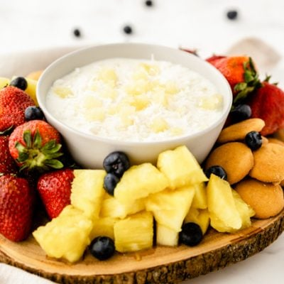 platter of fruit and snacks with white bowl of fruit dip