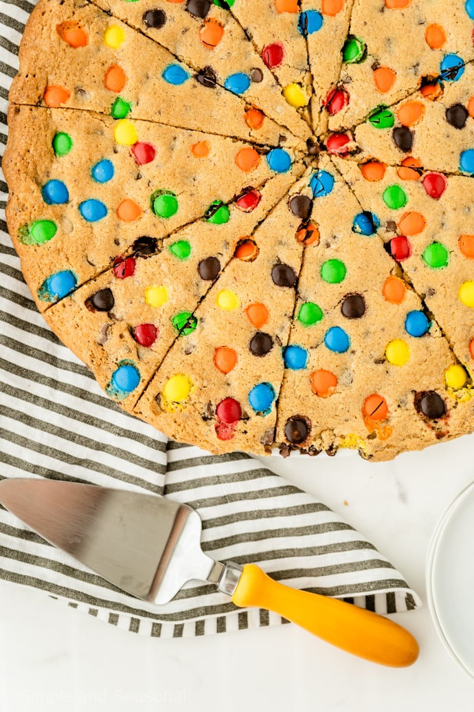 Giant Cookie Cake sliced like pizza with serving spatula and striped towel