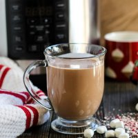 full mug of hot cocoa with Christmas mug in background and marshmallows and peppermint
