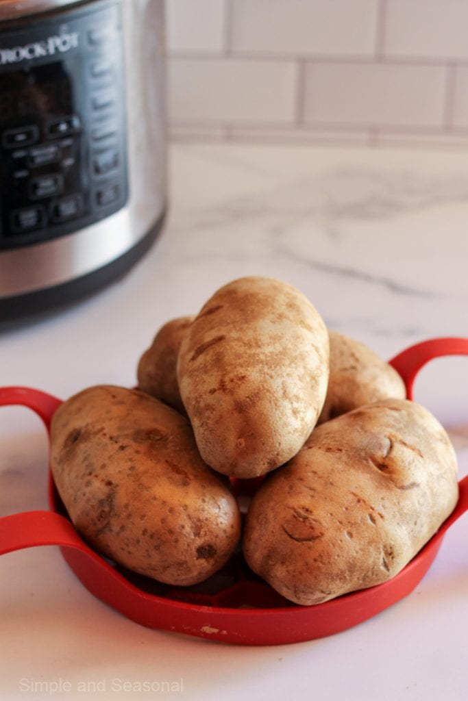 four raw potatoes stacked up on a red trivet