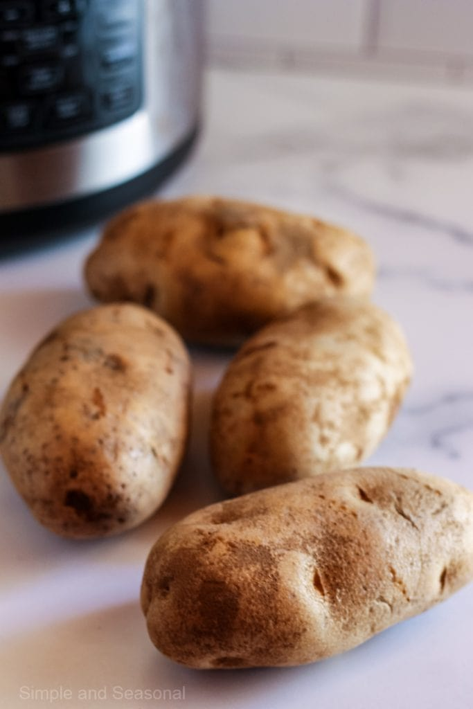 four uncooked potatoes with crockpot express in background