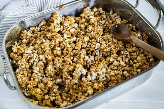 caramel mixture coated popcorn in a roasting pan