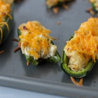 crack chicken jalapeno poppers on a baking sheet-one with a bite taken out of it