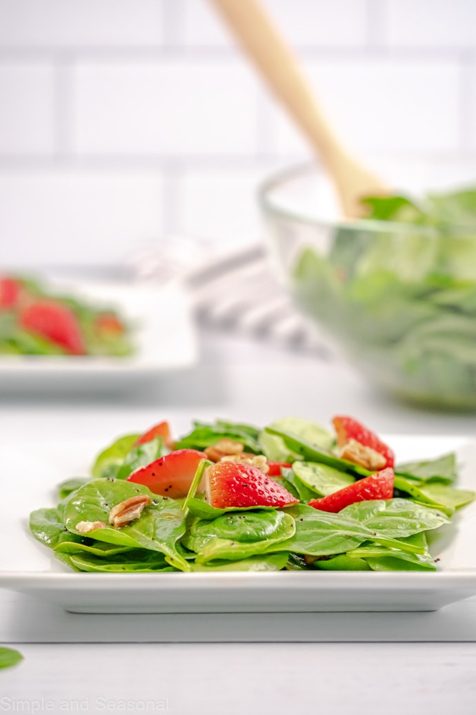 white plate with spinach strawberry salad and salad bowl in background