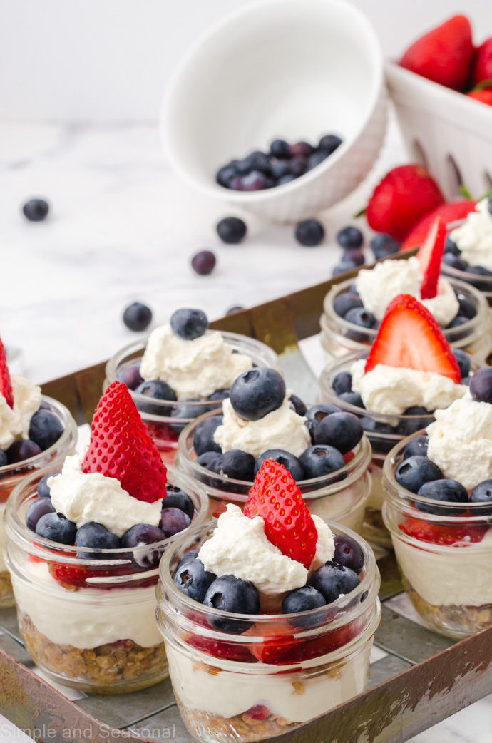 mini cheesecakes on a tray with blueberries and strawberries in the background
