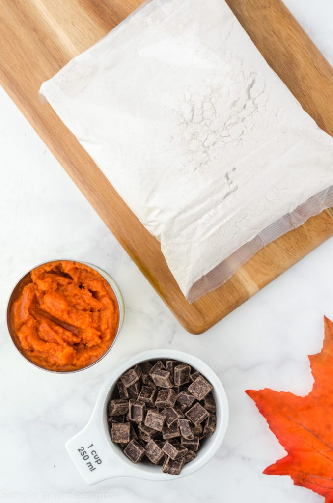 cake mix in the bag, pumpkin puree in a bowl and chocolate chunks in a bowl