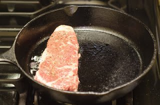 Raw steak in a super hot pan