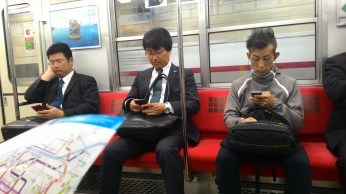 commuters busy with their cellphones