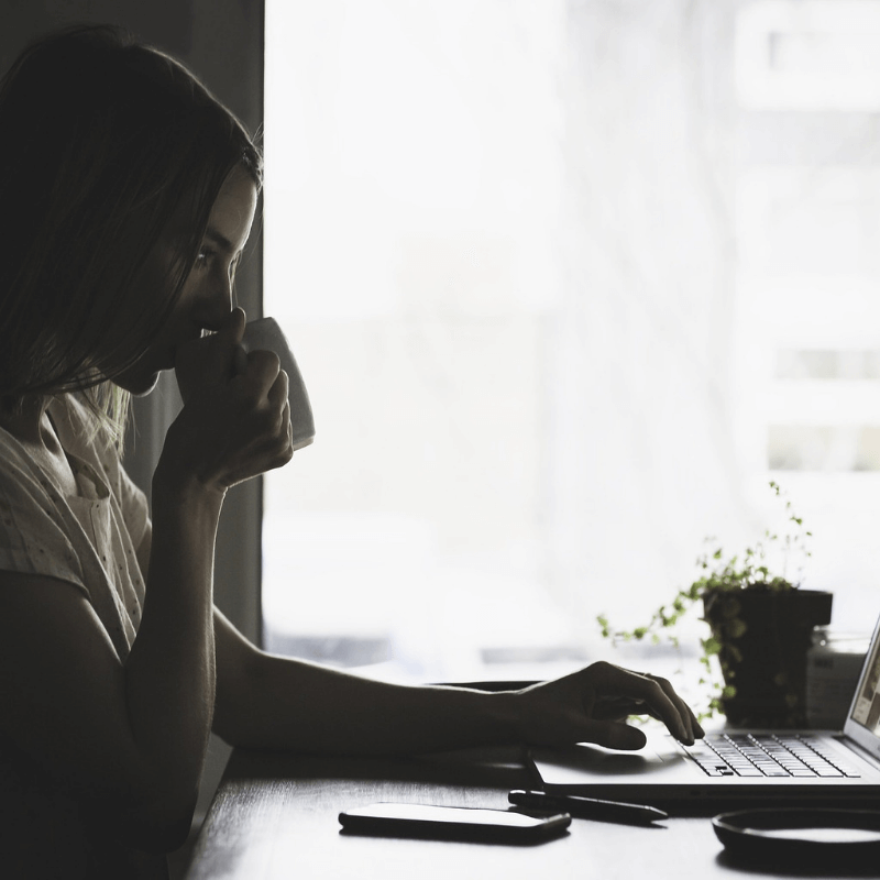 Post: Advice for new bloggers: How to be a real money making business. Picture of a women sipping tea and typing on laptop