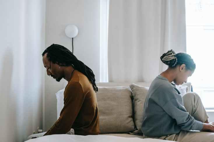 concerned black couple sitting on bed in misunderstanding