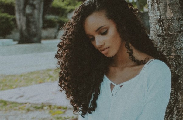 girl with curly hair sitting next to tree looking somber