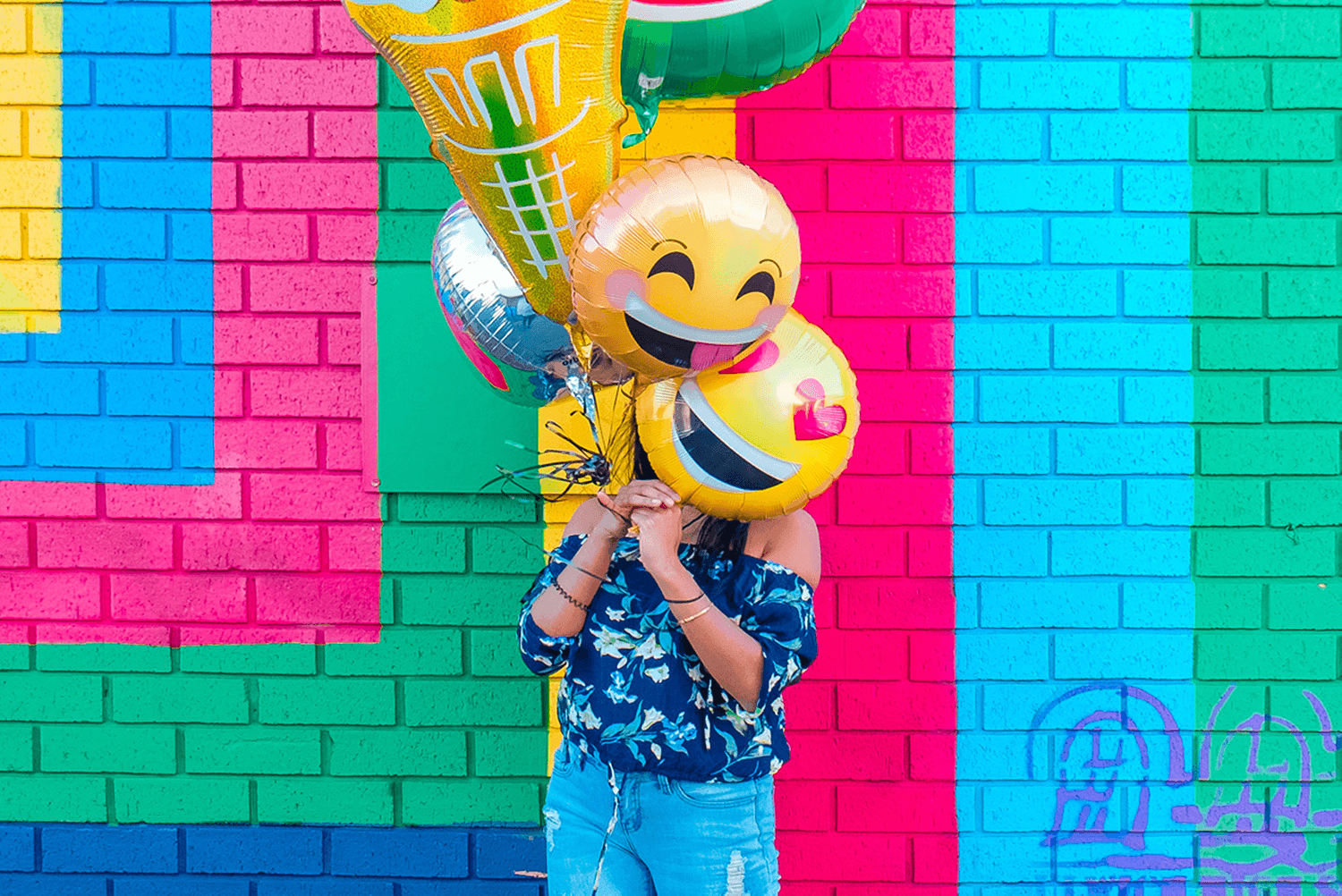 girl-holding-ballons-by-wall
