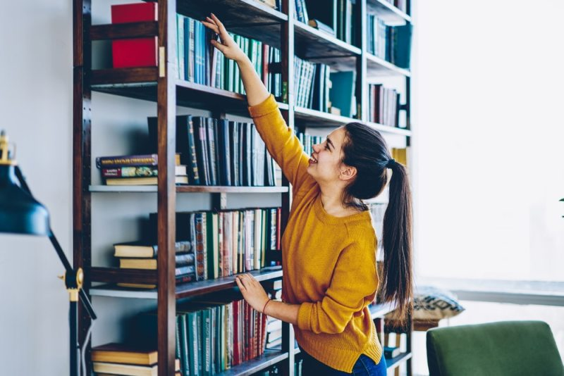 Woman reaching for book on shelf