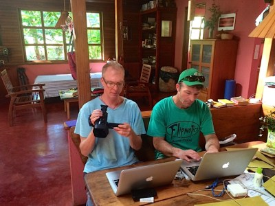 Stephen, with camera and computer, and Loudon, with computer, view and edit video footage for uploading via internet connection.