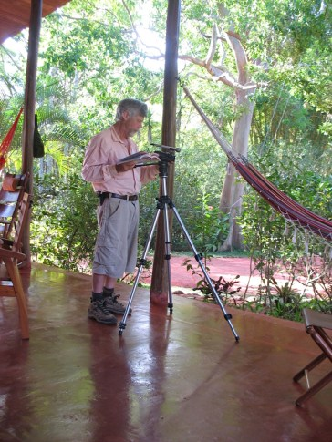 Photo of Michael Godfrey on the porch of the main house at Refugio de Los Angeles with video and audio recording devices on a tripod