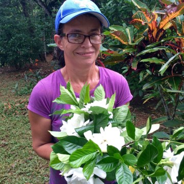 Photograph of long time Refugio de Los Angeles employee Sonia Ramirez with  a bouquet of fresh cut gardenias.