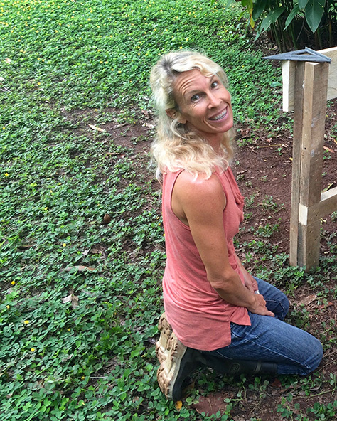 Photograph of Wendy Bishop, biologist, building a raised bed for vegetables