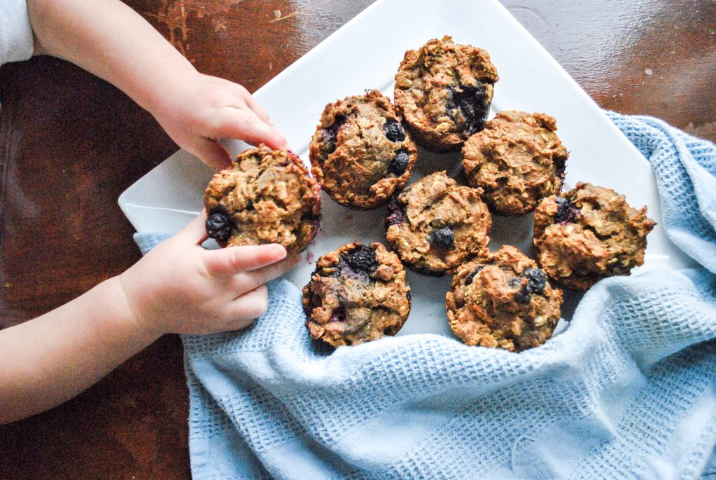 little girl reaching for blueberry muffins