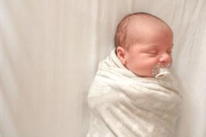 baby swaddled in grey blanket