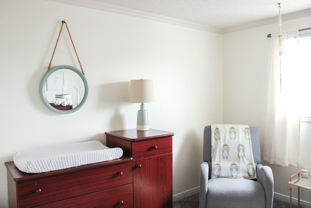 changing table, mirror, lamp, and rocking chair in nursery