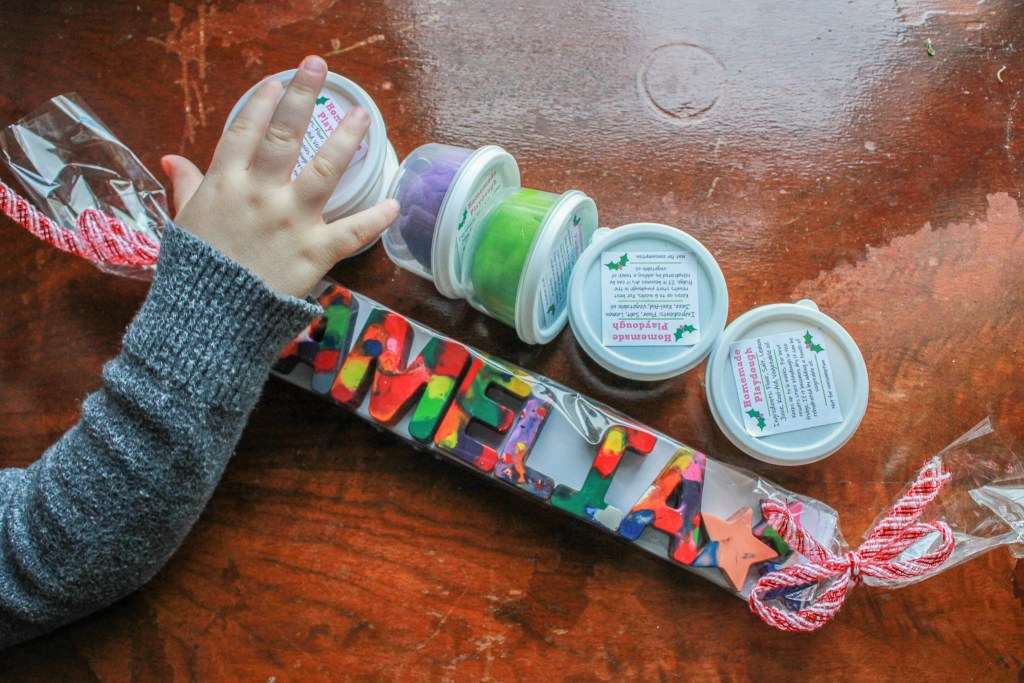 child's hand with personalized crayons and tubs of playdoh
