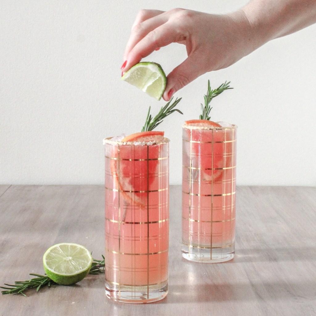 salt rimmed glasses of Grapefruit Paloma with springe of Rosemary