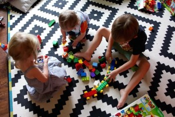 three toddlers playing lego