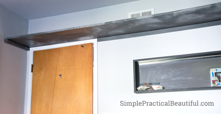 Create a frame with smaller boards to hold a wall-length shelf in place
