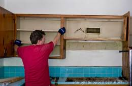 removing old kitchen cabinets that were nailed to the wall